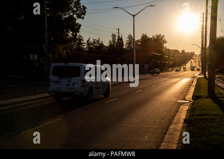 Colour horizontal image showing cars driving along long road towards sun that is low in the sky. - Stock Photo