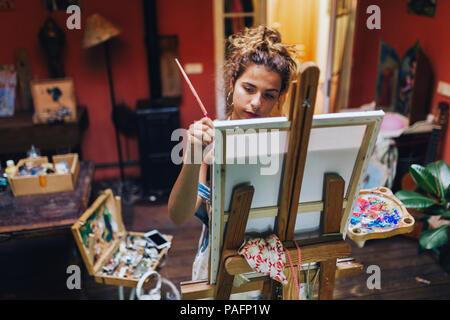 Indoor shot of professional female artist painting on canvas in studio with plants. - Stock Photo
