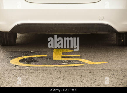 Car parked in disabled parking bay with disabled logo visible on the ground - Stock Photo