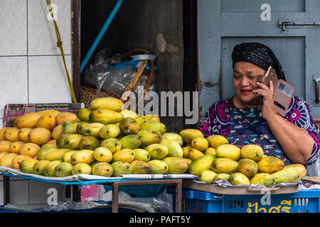 Bangkok, Thailand - May 1, 2018:: Local lady selling mangos on the street while speaking at the mobile phone - Stock Photo