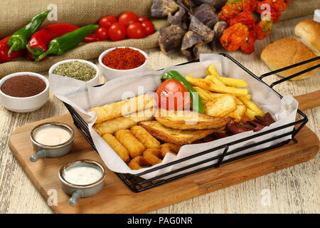 Mixed appetizer of french fries, fried sasusage, fried zucchini, pastry, sigara borek with sauces - Stock Photo