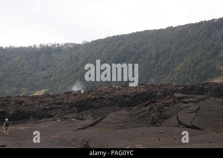 The tumultuous crater floor of the Kilauea Iki Crater with steaming vents and a male tourist in Hawaii, USA - Stock Photo