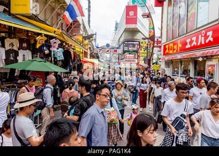 Crowded Tokyo street with shoppers on a Saturday afternoon and bright coloured shop fronts - Stock Photo
