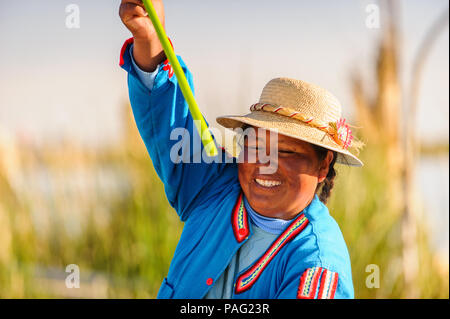 PUNO, PERU - NOVEMBER 7, 2010: Unidentified Peruvian woman in traditional clothes rows the boat in Uros Islands, Peru, Nov 7, 2010. Uros Islands iclud - Stock Photo