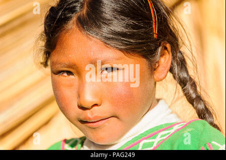 PUNO, PERU - NOVEMBER 7, 2010: Unidentified Uros girl who lives on the Uros Islands, Peru, Nov 7, 2010. Uros Islands iclude 42 floating islands. - Stock Photo