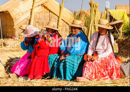PUNO, PERU - NOVEMBER 7, 2010: Unidentified Uros people in traditional clothes on the  Uros Islands, Peru, Nov 7, 2010. Uros Islands iclude 42 floatin - Stock Photo