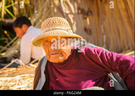 PUNO, PERU - NOVEMBER 7, 2010: Unidentified Uros woman in traditional clothes on the  Uros Islands, Peru, Nov 7, 2010. Uros Islands iclude 42 floating - Stock Photo