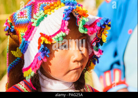 PUNO, PERU - NOVEMBER 7, 2010: Unidentified Uros girl in traditional clothes on the  Uros Islands, Peru, Nov 7, 2010. Uros Islands iclude 42 floating  - Stock Photo