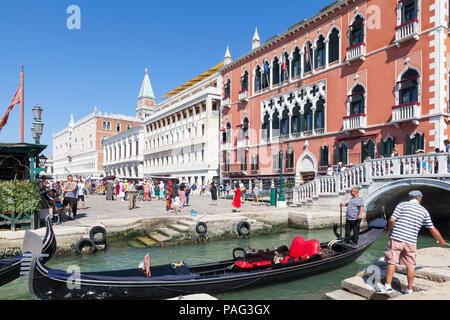 Gondolier in a colourful gondola waiting to exit Rio del Vin, Castello, Venice, Veneto, Italy after offloading tourists near the Danieli Hotel, Riva d - Stock Photo
