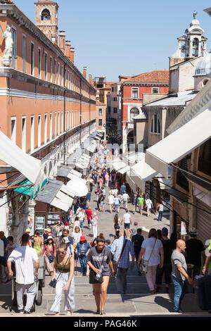 Tourists shopping at Rialto Mercato in the souvenir shops, San Polo, Venice, Veneto, Italy - Stock Photo