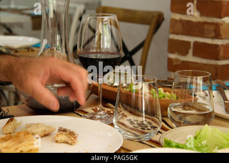 Close-up of dining table full of food and man's hand taking piece of food - Stock Photo