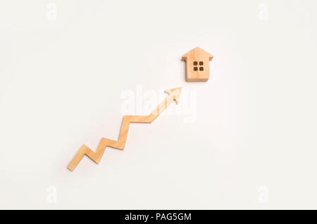 Wooden arrow up arrow points to a wooden house. The concept of revenue growth and cost. Increase the efficiency of business. Improving the quality of  - Stock Photo