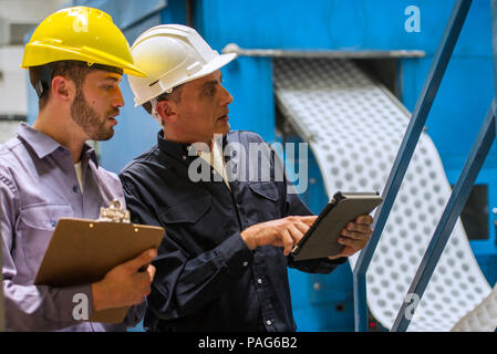 Factory workers discussing with each other in factory - Stock Photo