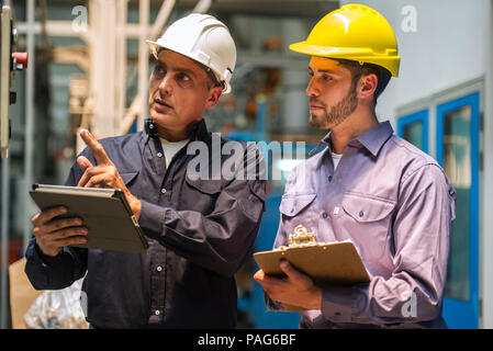 Factory workers examining control panel in factory - Stock Photo