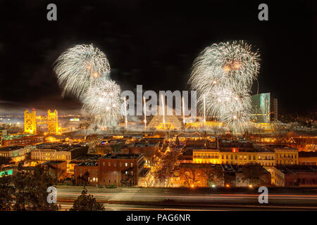 New Years Eve Fireworks in Sacramento, California over the river with a highway in the foreground. - Stock Photo