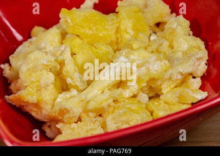A red bowl with scrambled eggs for breakfast on the kitchen table waiting to be eaten - Stock Photo