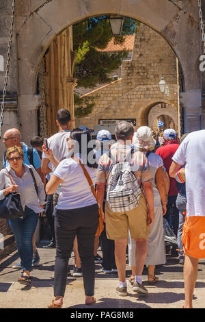 Tourists and visitors walking by the old architectural buildings near the Stradun street in Dubrovnik old town. Typical day in Dubrovnik, Croatia. - Stock Photo