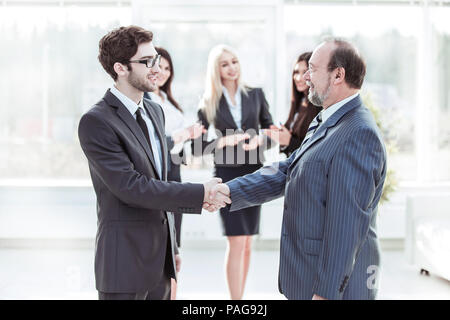 welcome and handshake of business partners on the background of applauding employees - Stock Photo