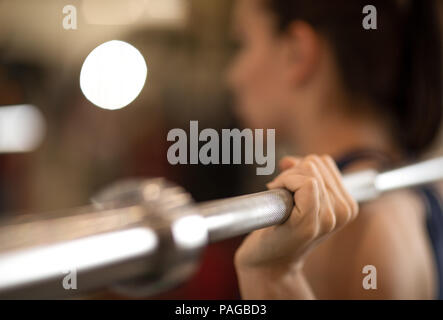 Young woman training with barbell in gym - Stock Photo