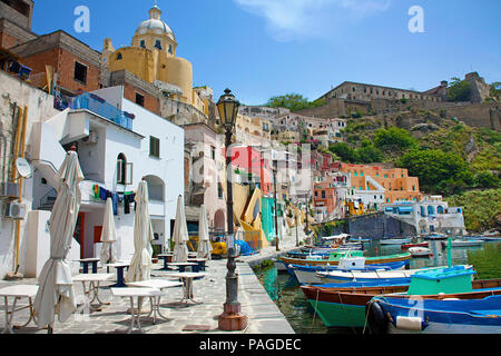 The idyllic fishing village Procida with fishing harbour Marina di Corricella, above the fortress Terra Murata, a former prison, Gulf of Naples, Italy - Stock Photo