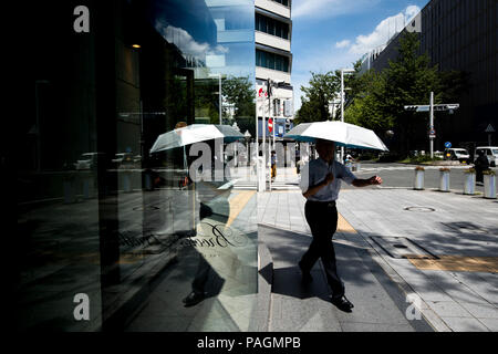 JULY 22, 2018 - A man walks in the shade in Nagoya, Japan. Temperatures in Nagoya reached 38.5 degrees Celsius on Sunday, as a nationwide heat wave continued to threaten health and safety. More than 40 people have died from heatstroke or related conditions since July 9, with thousands more hospitalized. Kyodo News reported 11 fatalities on Saturday alone. The Japan Meteorological Agency has forecasted continued high temperatures in the coming weeks. Credit: Ben Weller/AFLO/Alamy Live News - Stock Photo