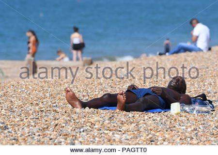 Brighton, East Sussex, UK. Monday 23rd July 2018. A man lays on the beach on another hot and sunny morning in Brighton. The temperature is expected to reach 24C today, reaching into the 30s by midweek. Credit: Geoff Smith / Alamy Live News - Stock Photo