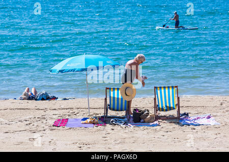 Bournemouth, Dorset, UK. 23rd July 2018. UK weather: the heatwave continues as temperatures rise on a scorching hot and sunny day at Bournemouth beaches with blue skies and unbroken sunshine. Sunseekers head to the seaside to soak up the sun. Woman on the beach with deckchairs and parasol, Credit: Carolyn Jenkins/Alamy Live News - Stock Photo