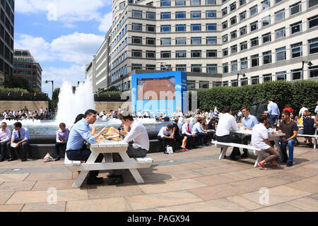 London. UK. 23rd July 2018. City workers enjoy their lunchbreak in the summer sunshine in Cabot Square, canry Wharf with temperatures expected to reach 35C this week and the Met Office issues an Amber weather warning for parts of Britain affected by the ongoing heatwave Credit: amer ghazzal/Alamy Live News - Stock Photo