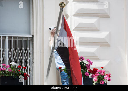 London, UK. 23rd July, 2018. A man adjusts a surveillance camera behind an Iraqi flag outside the Iraqi embassy. Credit: Mark Kerrison/Alamy Live News - Stock Photo