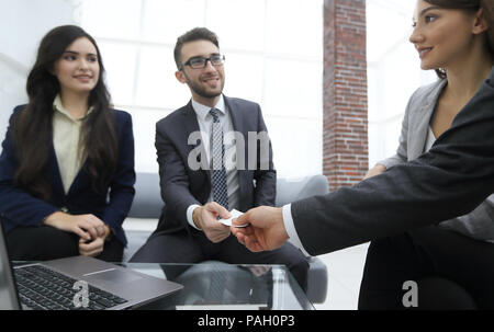 Close-up of two businesspeople exchanging visiting card - Stock Photo