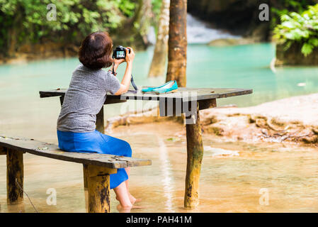 Woman near Kuang Xi Falls, waterfall in area mountain with forest, Luang Prabang, Laos. Copy space for text - Stock Photo