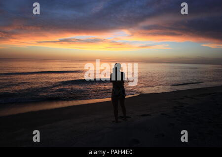 Woman in silhouette photographing the sunset over the Gulf of Mexico on Captiva Island off Florida's west coast, United States. - Stock Photo