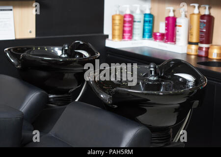 Photo of two black ceramical hair sinks standing in beaty salon with haircair products on background. Colorful plastic bottles for hair health. Modern interior done in dark colors. - Stock Photo
