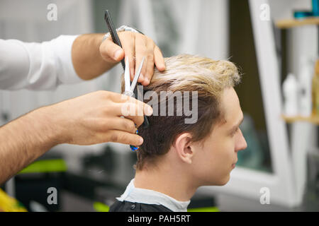 Close up of barber's hands doing new haircut for young client. Using black plastic comb, metallic sharp scissors. Male model having colored hair, looking forward. Working in barber shop. - Stock Photo