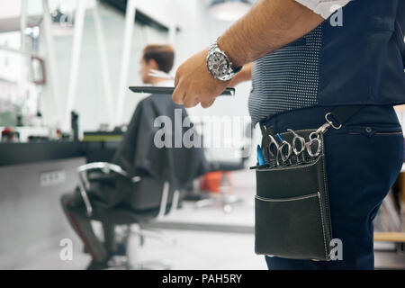 Close up of barber's leather bag with metallic sharp scissors for haircutting. Hairstyler wearing dark blue trousers, grey waistcoat, handwatch. Keeping black plastic comb. Client sitting behind. - Stock Photo