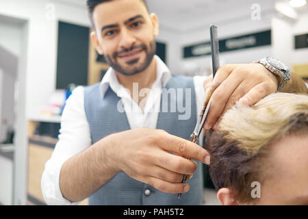 Doing new hairstyle for male model using sharp metallic scissors. Hairdresser wearing classic white shirt, grey waistcoat. Smiling, looking at camera, loving his job. Male model having toned hair. - Stock Photo