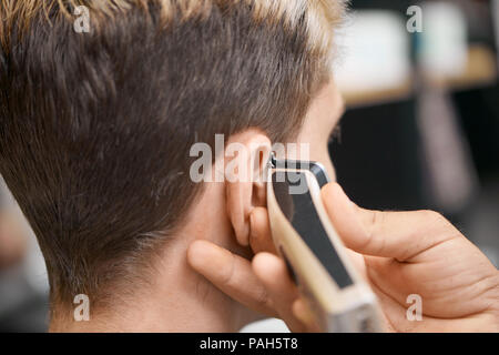 Barber's hand using hair clipper, doing new haircut for client sitting in front of mirror. Model having dark, toned hair, looking forward. Working in modern spacy barber shop, beaty salon. - Stock Photo