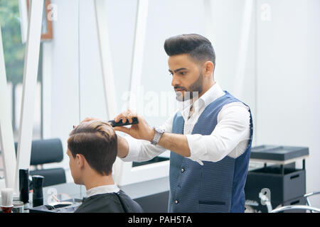 Barber doing new haircut for young client using black plastic comb. Wearing white casual shirt, grey waistcoat, watch. Looking concentrated, loving his job. Model covered with special black cape. - Stock Photo