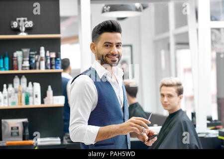 Smiling barber standing near client sitting near mirror, looking at camera. Wearing casual white shirt, stylish grey waistcoat. Posing in front of shelves with hair care products. Feeling positive. - Stock Photo