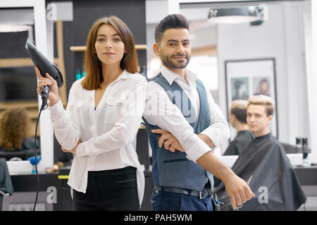 Two hairstylers posing standing in modern beaty salon, young client sitting behind. Hairdressers wearing classic white shirts, man having grey waistcoat. Woman keeping hair dryer, looking at camera. - Stock Photo