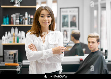 Female hairdresser posing in front of young male client sitting near big mirror and shelves with hair care products. Hairstyler wearing white casual shirt and looking at camera, smiling. - Stock Photo