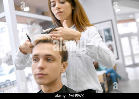 Front view of female hairstyler doing haircut for young boy. Working in spacy beaty salon. Male model looking forward. Master using sharp metallic scissors and black comb. Wearing white shirt. - Stock Photo
