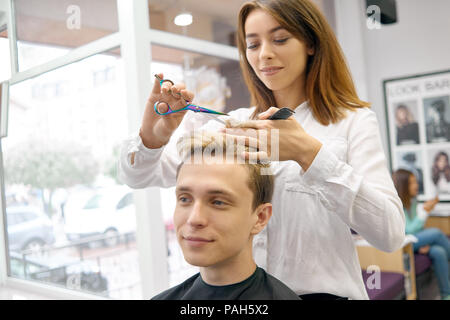 Female hairstylist doing haircut for handsome model with toned lilac. Hairdresser using sharp metallic scissors and black plestic comb. Master wearing white shirt and looking at camera. - Stock Photo