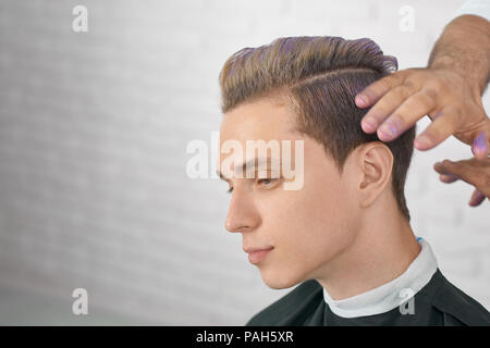Young male model waiting for new hairstyle with lilac hair coloring. Hairdresser's hands doing stylish coloring for handsome boy. Working on white brick studio background. - Stock Photo