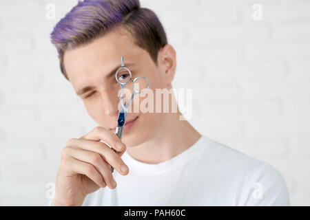 Young hairstylist with toned in violet color hair looking at camera through little hole in sharp scissors for hairdressing. Boy wearing white casual tshirt. Feeling good, optimistic, looking original.