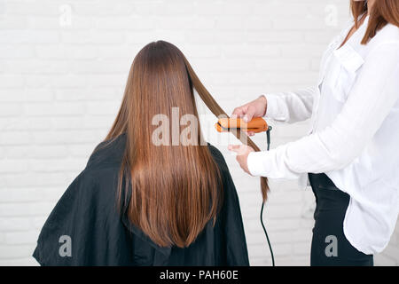 Model sitting while hairstyling in beaty salon with white brick walls. Wearing black cape for hairdressing. Girl having dark, long, glancy, straight, brown hair. Hairdresser using hair flatter. - Stock Photo