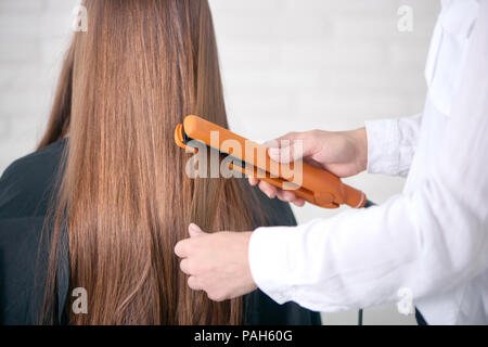 Back view of hairdresser straighting client's long brown hair. Model having smooth, straight, glancy, healthy hair, sitting covered with special black cape. Hairstyler wearing white classic shirt. - Stock Photo