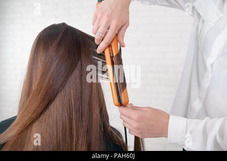 Hairstylist working with client brown hair, keeping straightener, making curles. Model having long, dark, straight, smooth, glancy hair. Hairdresser wearing classic white shirt. white background. - Stock Photo