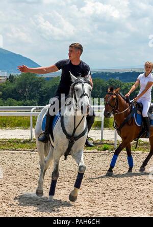 PYATIGORSK, RUSSIA - JULY 22, 2018:Beautiful men show elements of jiggery, riding a brown horse on racecourse Pyatigorsk. - Stock Photo