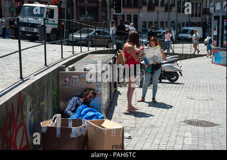 15.06.2018, Porto, Portugal, Europe - Two female tourists are seen studying a city map of Porto while a homeless man lies directly next to them. - Stock Photo
